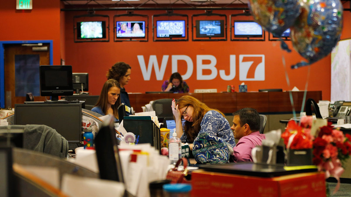 Members of the WDBJ-TV7 news staff prepare for the early morning newscast at the station, Thursday, Aug. 27, 2015, in Roanoke, Va. Reporter Alison Parker and cameraman Adam Ward were killed by a former colleague during a live broadcast Wednesday, while on assignment in Moneta. The balloons and flowers, at right, are addressed to Ward's fiancee, Melissa Ott, who was celebrating her last day at WDBJ on Wednesday, before moving to a station in North Carolina.