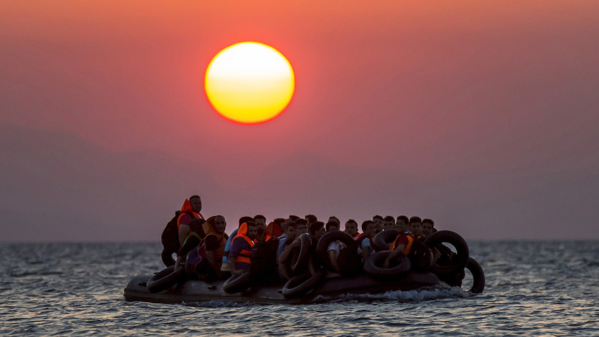 File - Migrants on a dinghy arrives at the southeastern island of Kos, Greece, after crossing from Turkey, Thursday, Aug. 13, 2015. Migrants by the tens of thousands are braving the perilous journey across the Mediterranean this year, hoping to reach Europe and be granted asylum.