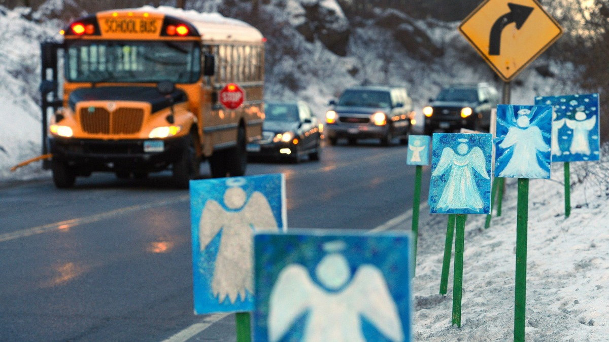 In this Jan. 3, 2013, file photo, a bus traveling from Newtown, Conn., to Monroe stops near 26 angel signs posted along the roadside in Monroe, Conn., on the first day of classes for Sandy Hook Elementary School students since the Dec. 14, 2012, shooting.