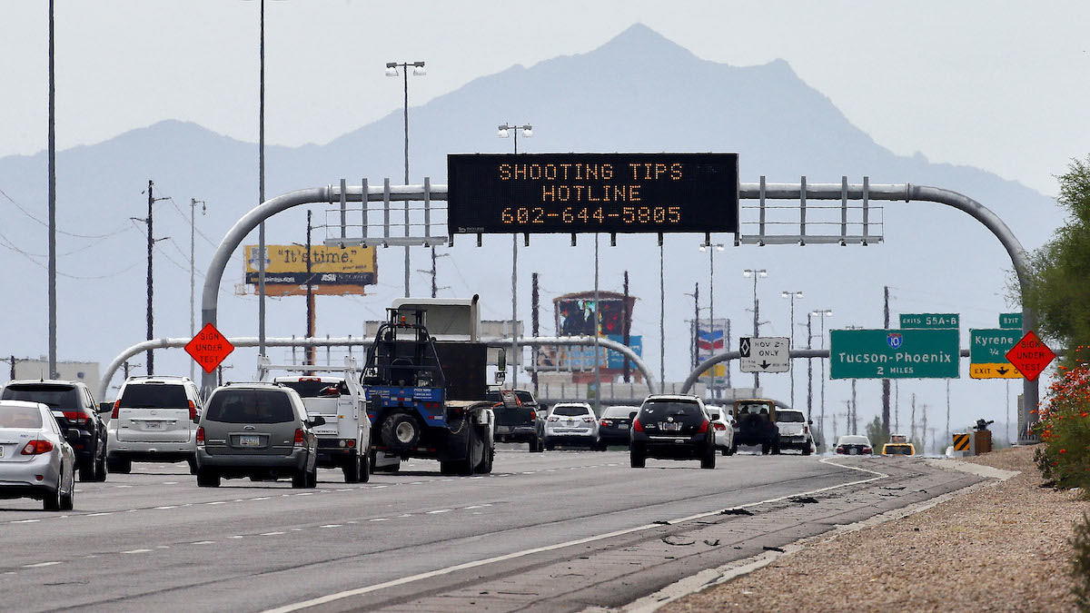 An Arizona Department of Transportation sign gives a hotline number for information on the recent freeway shootings as motorists pass under at the 202/I-10 intersection, Wednesday, Sept. 9, 2015 in Chandler, Ariz.
