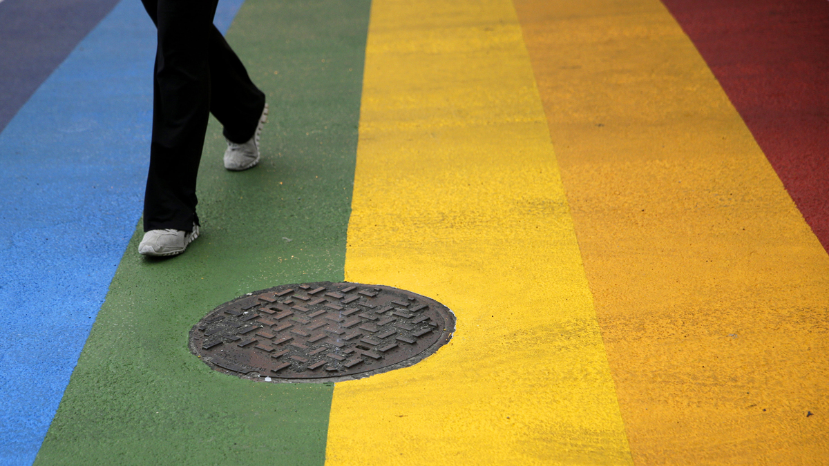 A woman walks across a rainbow crosswalk in support of the LGBT community at the intersection of 13th and Locust streets, Thursday, June 25, 2015, in Philadelphia. (AP Photo/Matt Slocum)