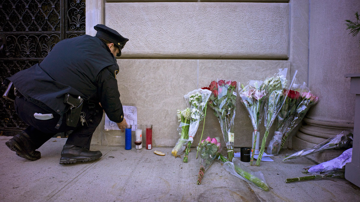 A New York City police officer adjusts parts of a make shift memorial left as a sign of support to France near the door of the French consulate in New York, Saturday, Nov. 14, 2015. French officials say several dozen people were killed in shootings and explosions at a theater, restaurant and elsewhere in Paris on Friday.