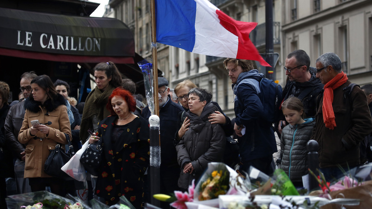 People gather in front of Le Carillon cafe, a site of the recent attacks, in Paris, Monday Nov. 16, 2015. French President Francois Hollande says the Paris attacks targeted