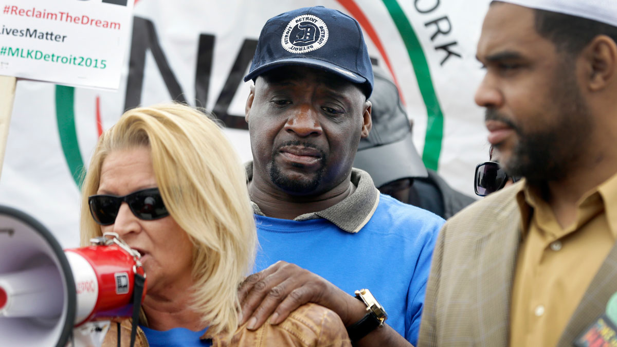 Floyd Dent, stands behind his attorney as she addresses hundreds of protesters after a march on Michigan Ave. on Friday, April 3, 2015 in Inkster, Mich. Dent was pulled from his car in January, repeatedly punched in the head by a white police officer and subdued with a stun gun in suburban Detroit.