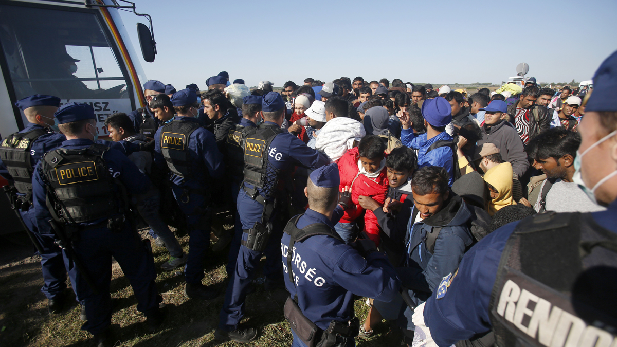 Hungarian police officers stop a group of migrants before a bus that would take them in Roszke, southern Hungary, Wednesday, Sept. 9, 2015.