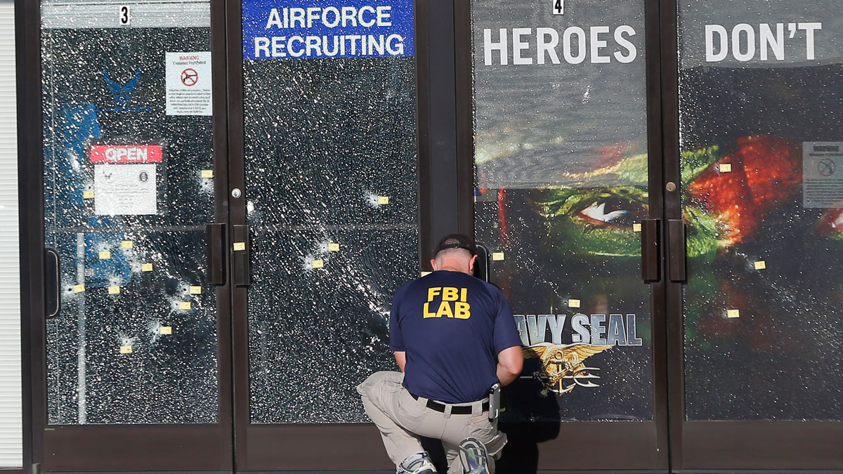 An FBI investigator works to gather evidence outside a military recruiting center on Friday, July 17, 2015, in Chattanooga, Tennessee.