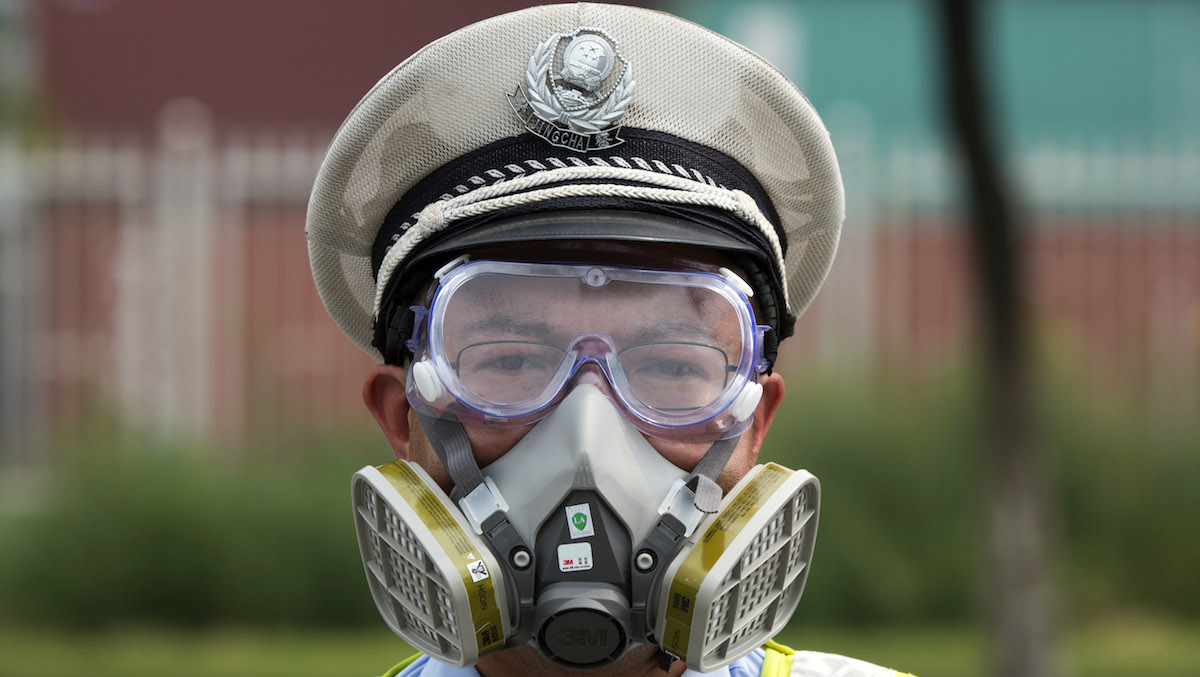 A Chinese traffic police man wears a mask at a security checkpoint near the site of an explosion in northeastern China's Tianjin municipality Saturday, Aug. 15, 2015.