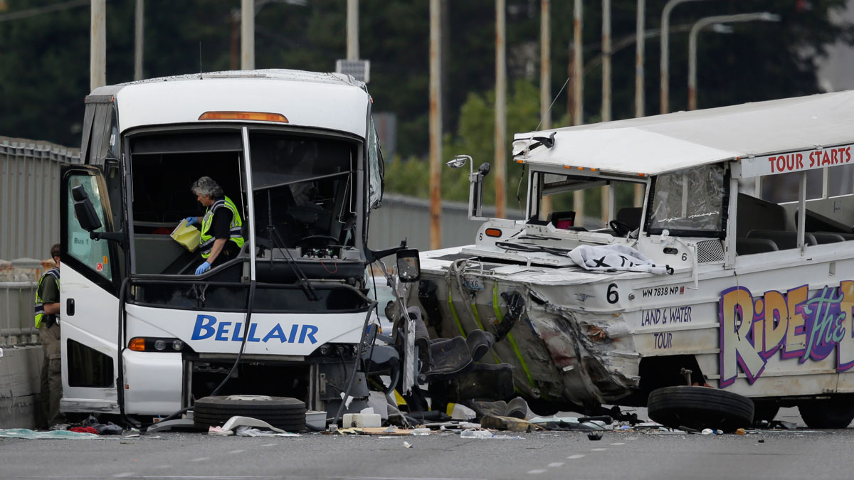 A Seattle Police investigator walks off of a charter passenger bus at left that was involved in a fatal crash with the Ride the Ducks tourist vehicle at right, Thursday, Sept. 24, 2015, in Seattle.