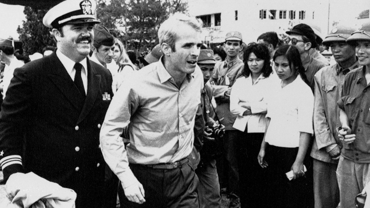 John S. McCain is escorted to Hanoi's Gia Lam Airport on March 14, 1973 after MCCain was released as a POW.