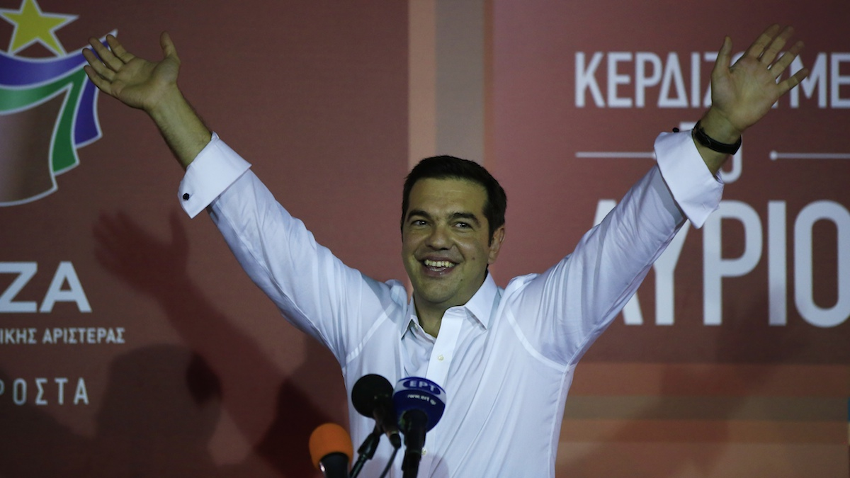 Left-wing Syriza party leader Alexis Tsipras waves to his supporters at Syriza's party's main electoral center in Athens, Sunday, Sept. 20, 2015. Tsipras who won Greece's parliamentary election for the second time this year on Sunday, says he will form a coalition government with the small right-wing Independent Greeks. (