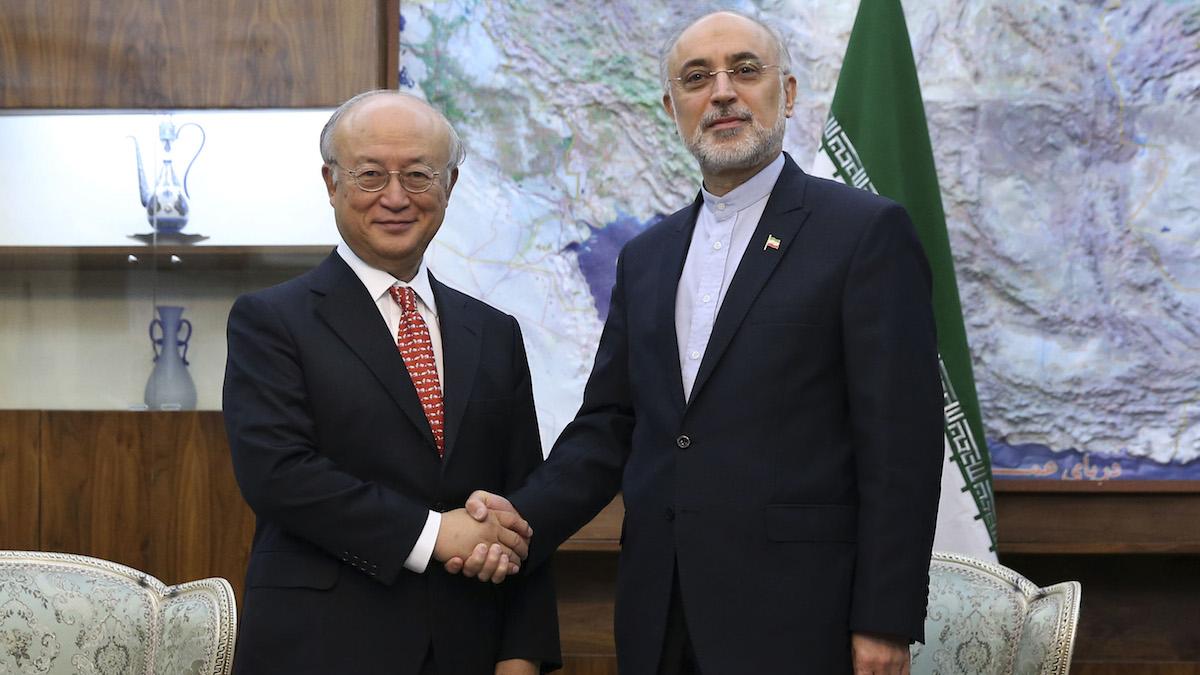 Head of Iran's Atomic Energy Organization Ali Akbar Salehi, right, and Director General of the International Atomic Energy Agency (IAEA) Yukiya Amano shake hands for the media during their meeting in Tehran, Iran, Sunday, Sept. 20, 2015.
