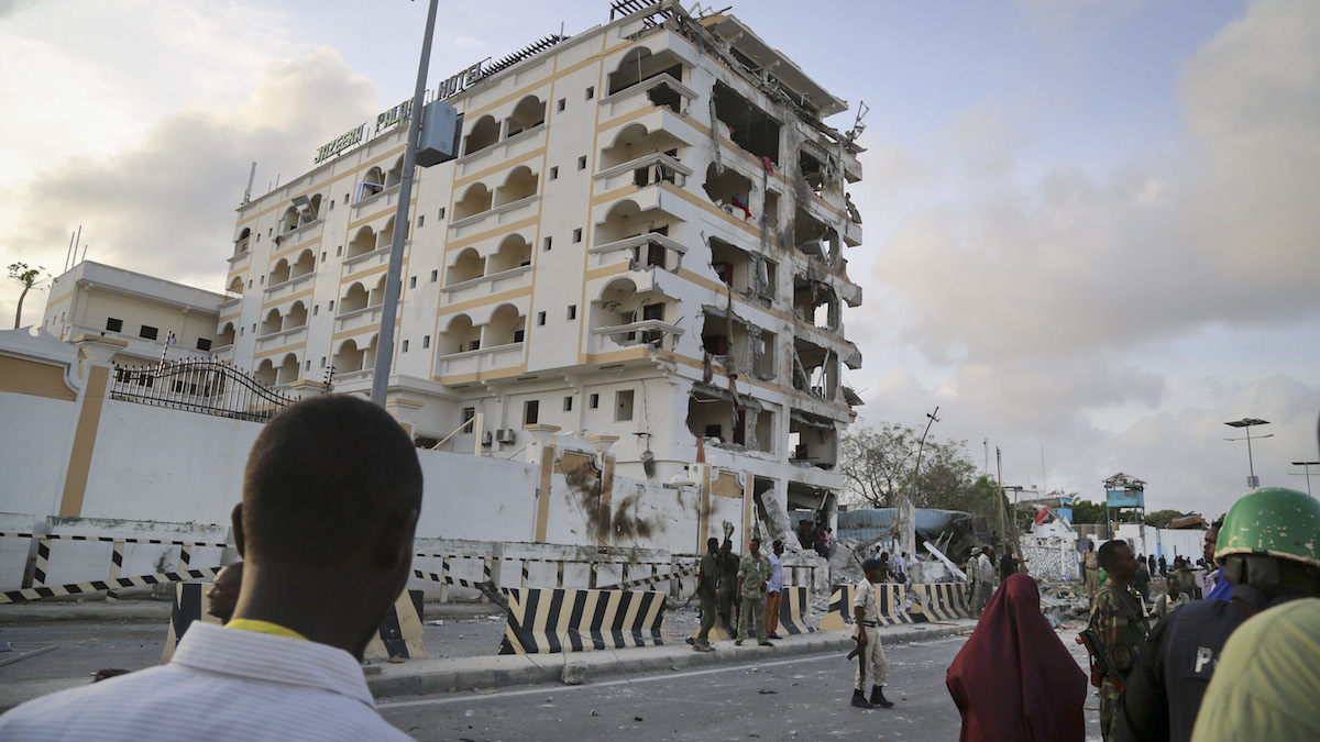 Somalis observe the destruction as security forces secure the scene of a suicide car bomb attack in the capital Mogadishu, Somalia, Sunday, July 26, 2015.  Somali police officer says a suicide car bomber has rammed his car into the protective perimeter outside a well-known hotel in the Somali capital Sunday, killing at least four people. Capt. Mohamed Hussein says the blast has caused an extensive damage on the Jazeera Hotel, which is often frequented by government officials, diplomats and foreigners. (AP Photo/Mohamed Sheikh Nor)