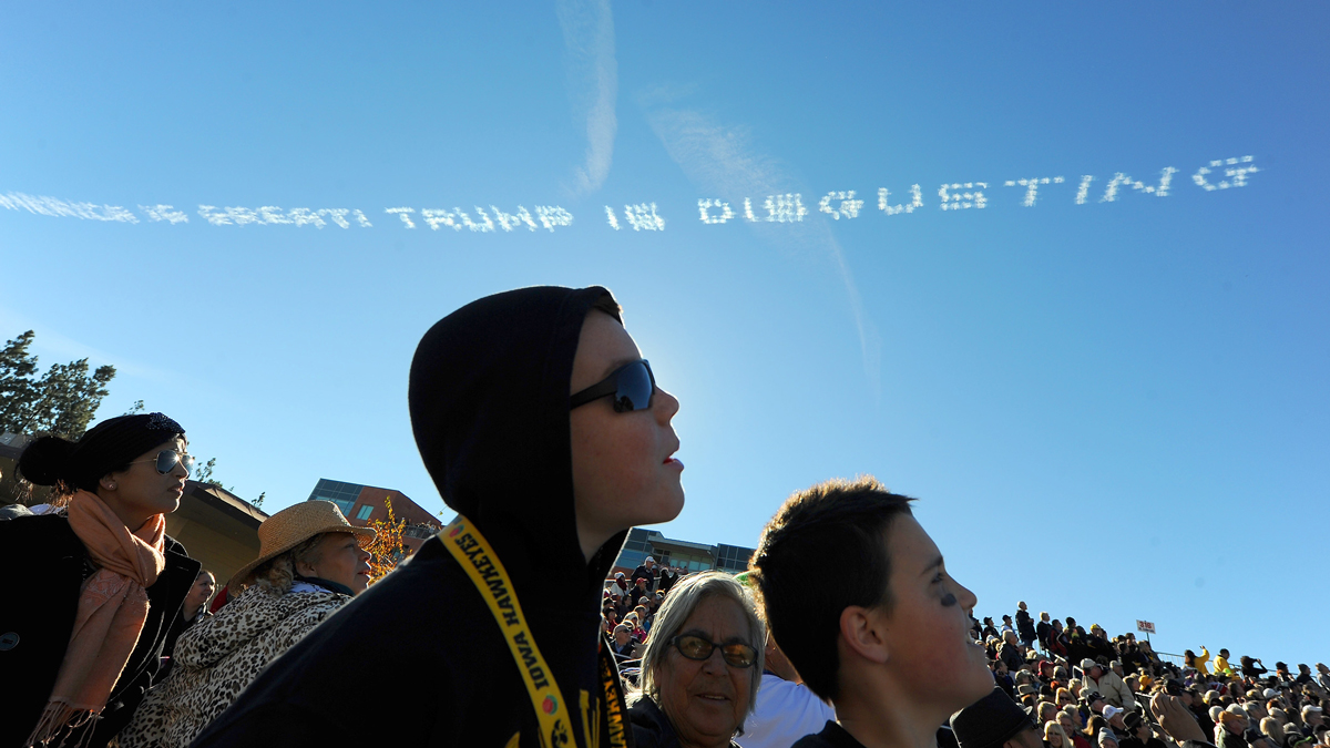 Parade spectators watch as airplane sky writers write a message