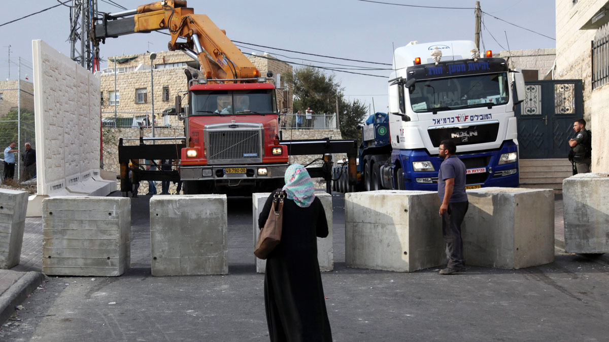 Palestinians watch a wall being built between Palestinian and Jewish neighborhoods in Jerusalem Sunday, Oct. 18, 2015.