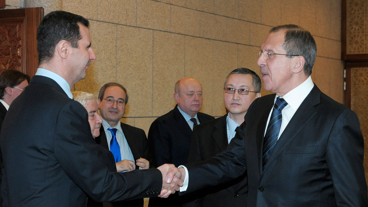 FILE - In this Feb. 7, 2012 file photo, Syrian President Bashar Assad, left, shakes hands with Russian Foreign Minister Sergey Lavrov after talks in Damascus, Syria. Lavrov said Thursday, Sept. 10, 2015, that Russian aircraft flying into Syria have been delivering weapons along with humanitarian supplies.