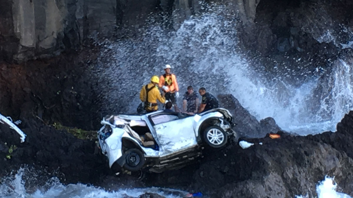 In this May 29, 2016, photo provided by Tom Johnson, rescue workers respond to the scene of a car crash off Maui's Hana Highway in Hana, Hawaii.