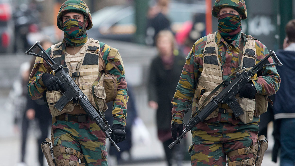 Belgian soldiers patrol outside a court building where Salah Abdeslam, the top suspect in last year's deadly Paris attacks, was expected to appear before a judge in Brussels, Belgium, Thursday, March 24, 2016. Authorities in Belgium detained seven people early Friday in connection with Brussels blasts.