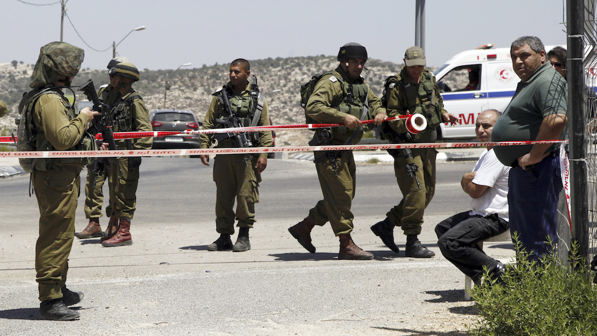 Israeli soldiers secure the scene after a  Palestinian man wounded an Israeli soldier with a knife at a crossing between Israel and West Bank north of Jerusalem Saturday, Aug. 15, 2015. The attacker was shot and wounded by the troops.