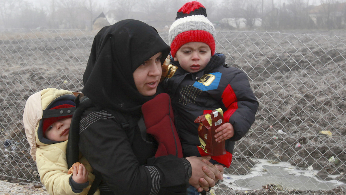 A Syrian refugee woman with babies walks towards the border with Serbia from the transit center for refugees near northern Macedonian village of Tabanovce, while on their journey through the so-called Balkan migrant corridor, Thursday, Jan. 28, 2016. Greek authorities say neighboring Macedonia has stopped Wednesday letting in refugees heading north to central Europe, leaving about 2,600 people stranded on the Greek side of the border. (AP Photo/Boris Grdanoski)
