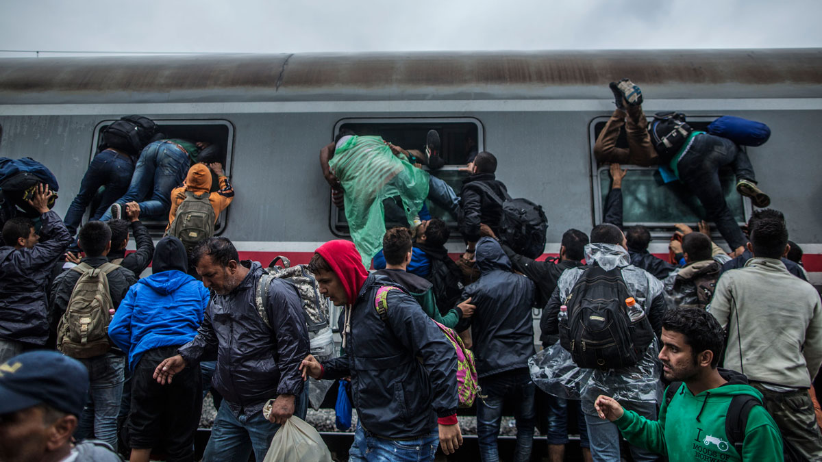 Migrants and refugees board a train by climbing through the windows as they try to avoid a police barrier at the station in Tovarnik, Croatia, Sunday, Sept. 20, 2015. Police said Saturday more people are coming in from Serbia, mostly near the eastern border town of Tovarnik, where there are already around 2,500 people waiting for transport.
