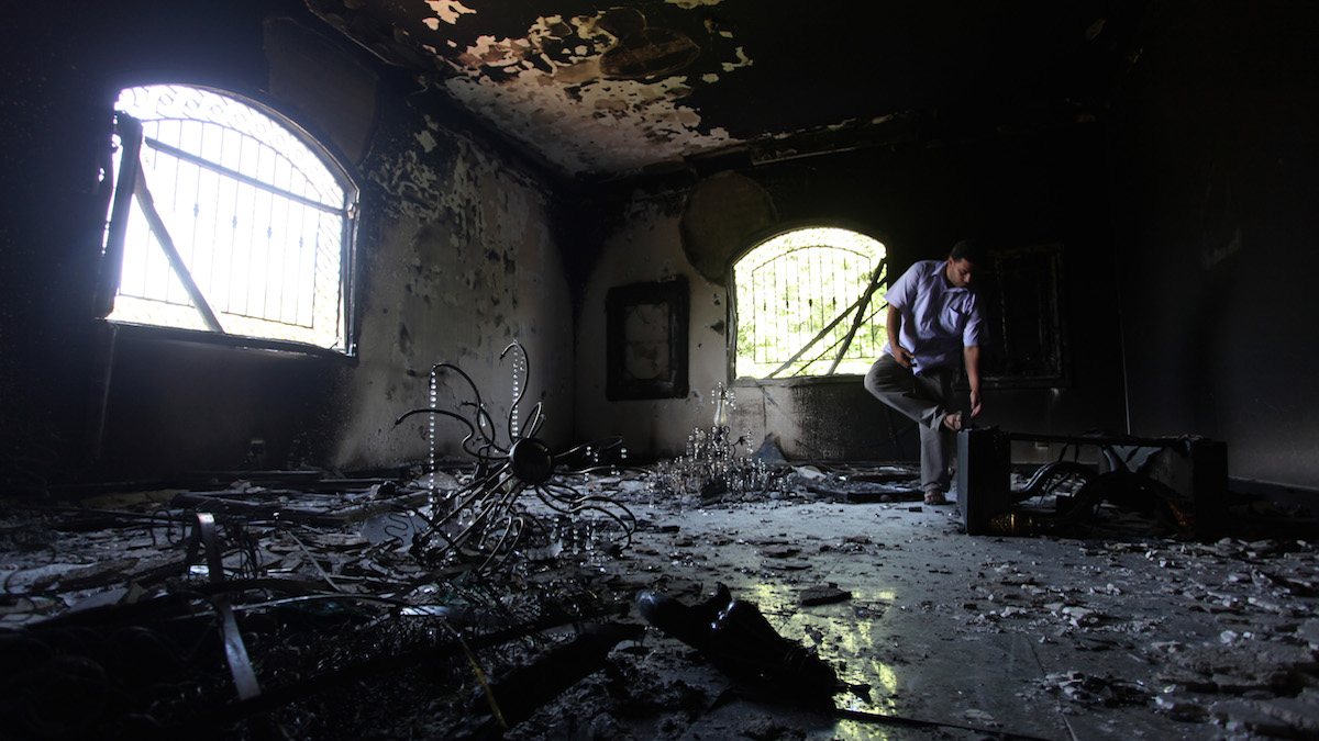 """FILE - This Sept. 13, 2012 file photo shows a Libyan man investigating the inside of the U.S. consulate in Benghazi, Libya, after a deadly attack two days earlier. Factions of the group in 2014 pledged allegiance to the Islamic State group. Even before the film's release, Hollywood director Michael Bay's new action movie is stirring controversy among government officials and residents of Benghazi, Libya's second-largest city and the birthplace of the uprising against longtime dictator Moammar Gadhafi. The film, """"13 Hours: The Secret Soldiers of Benghazi,"""" depicts the events of the 2012 attack on the U.S. consulate that killed four Americans, including Ambassador J. Christopher Stevens. It is set to be released in January 2016."""