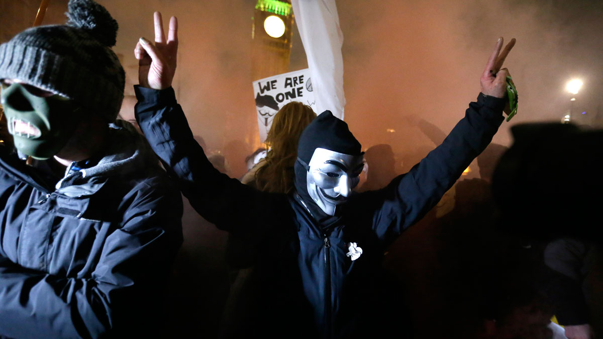 Masked demonstrators holds a flare during the Million Mask protest march in London on Thursday Nov. 5, 2015. Thousands of people dressed in Guy Fawkes masks are being met by 'significant policing operation', including thousands of extra officers to tackle expected unrest in this annual march that coincides with the Nov. 5 Bonfire Night celebration.