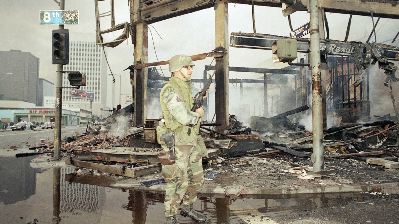 A National Guardsman patrols a burned area near Wilshire and Vermont in Los Angeles, Thursday, May 1, 1992 as rioting broke out following the outcome of the Rodney King beating trial.