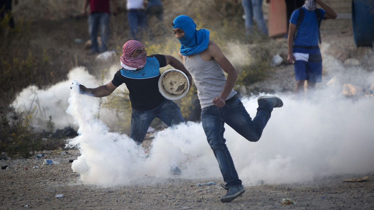 A Palestinian protester throws back a tear gas canister that was fired by Israeli troops during clashes near Ramallah, West Bank, Thursday, Oct. 15, 2015. In the current wave of violence, eight Israelis have been killed in stabbing and shooting attacks, as of Thursday. Thirty-one Palestinians have been killed, including 14 identified by Israel as attackers, and the others in clashes between stone-throwers and Israeli troops.