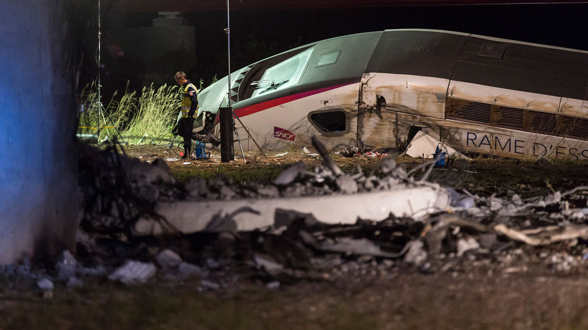 A rescue worker stands near a high-speed train which derailed in Eckwersheim, near Strasbourg, eastern France, Saturday Nov.14, 2015. An official says a high-speed train undergoing a test run has derailed and plunged into a canal in northeast France, killing at least seven people and gravely injuring at least a dozen others.