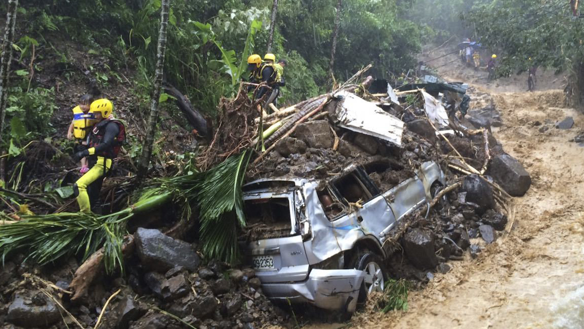In this image released by the New Taipei Fire Department, emergency rescue personnel carrying children pass crushed cars from a flash mudslide caused by Typhoon Soudelor in Xindian, New Taipei City, northern Taiwan, Saturday, Aug. 8, 2015. At least four people were killed and four were missing when powerful Typhoon Soudelor slammed into Taiwan, authorities said Saturday.