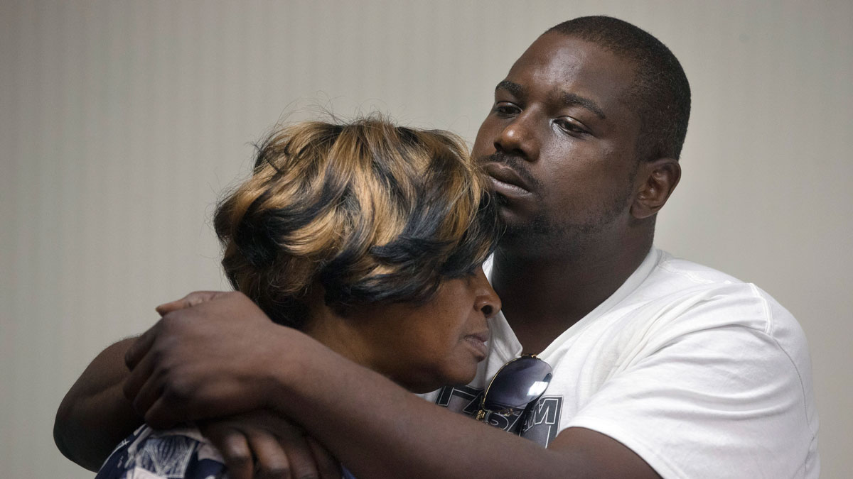 Aubrey DuBose, right, holds his mother Audrey during a news conference after murder and manslaughter charges against University of Cincinnati police officer Ray Tensing were announced for the traffic stop shooting death of motorist Samuel DuBose, Wednesday, July 29, 2015, in Cincinnati. Hamilton County Prosecutor Joseph Deters added that the officer
