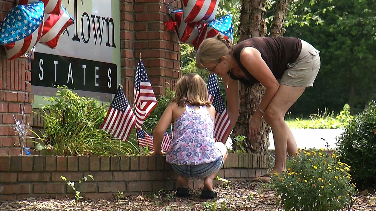 In this image made from video, Paige Shartle, 10, and Debbie Shartle, 51, pay their respects at a memorial at the entrance of Navy Petty Officer 2nd Class Randall Smith's neighborhood in Rossville, Ga. on Saturday, July 18, 2015. Smith, who was shot in the attack on a military facility in Chattanooga, Tennessee, on Thursday, July 16, 2015, died two days after a gunman killed four Marines during a shooting rampage on two military facilities