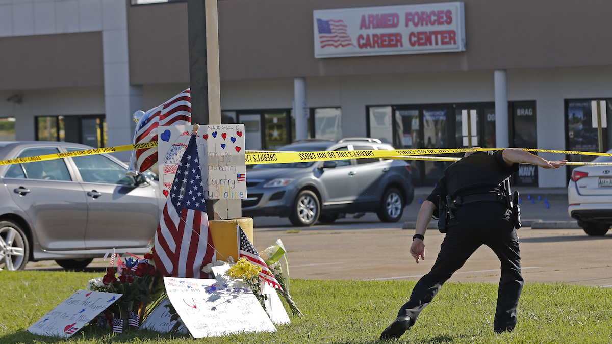 A police officer ducks under tape near a memorial in front of an Armed Forces Career Center on Thursday, July 16, 2015, in Chattanooga, Tenn. A gunman unleashed a barrage of fire at the center and another U.S. military site a few miles apart in Chattanooga, killing several and sending service members scrambling for cover as bullets smashed through the windows. The attacker was also killed.