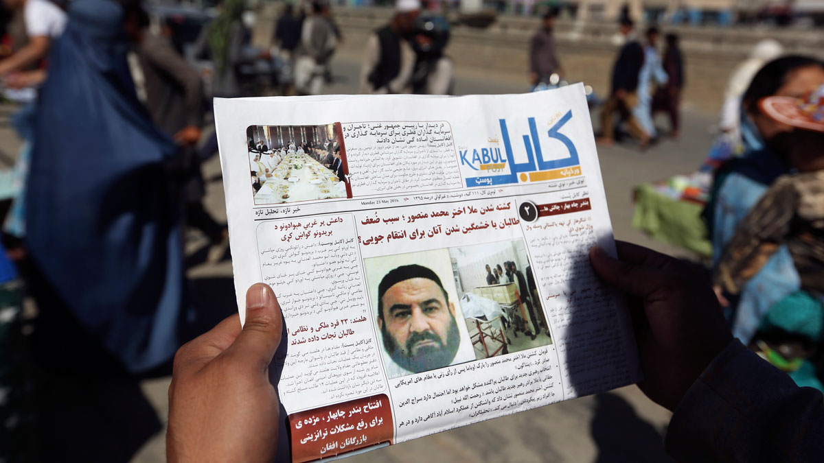 In this May 25, 2016, file photo, an Afghan man reads a local newspaper with photos the former leader of the Afghan Taliban, Mullah Akhtar Mansoor. A senior U.S. defense official says the administration is moving toward a decision to expand the military's authority to conduct airstrikes against the Taliban in Afghanistan.