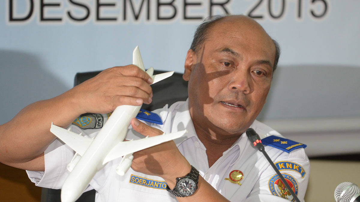 Indonesian Soejanto Tjahjono, head of the National Transportation Safety Committee (KNKT), holds a plane model as he speaks to journalists in Jakarta on December 1, 2015, during a press conference on the investigation report of AirAsia flight QZ8501 that crashed into the Java sea on December 28, 2014. Faulty equipment and the crew's