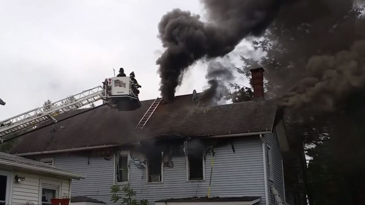 Smoke pouring from the roof of a house on Hubbell Avenue in Ansonia Tuesday morning.