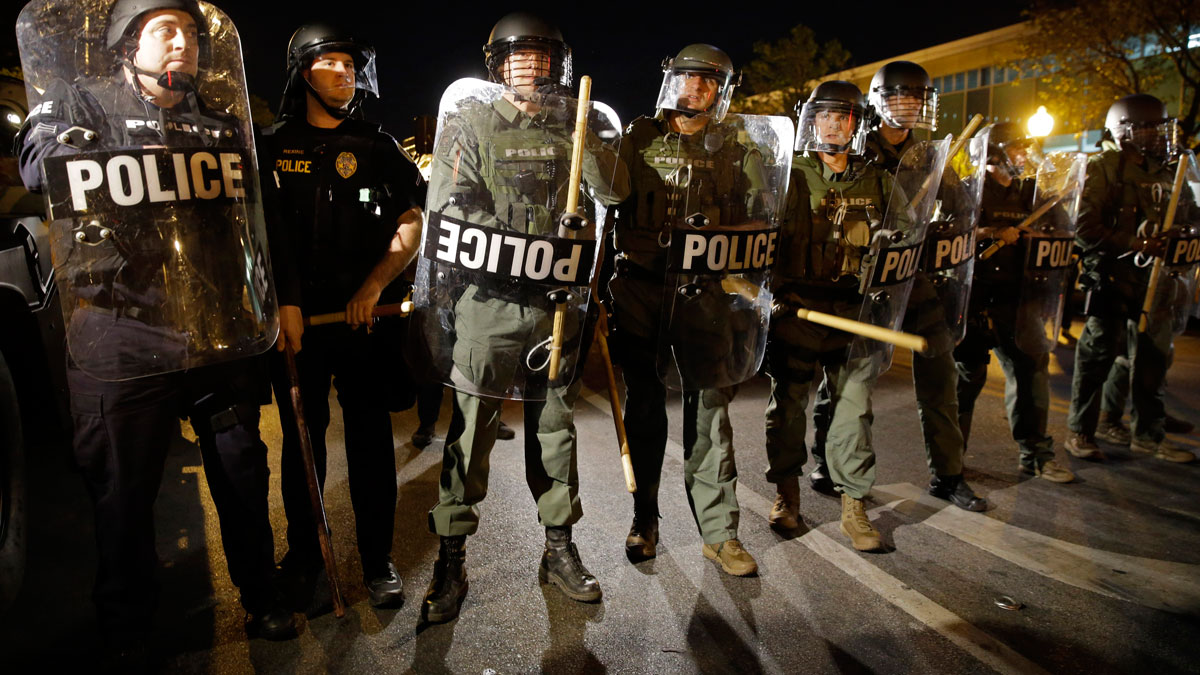 In this April 29, 2015, file photo, police stand in formation as a curfew approaches in Baltimore amid unrest. In August 2016, elected officials and others were upset to learn of a secret surveillance program later from a Bloomberg Businessweek article.