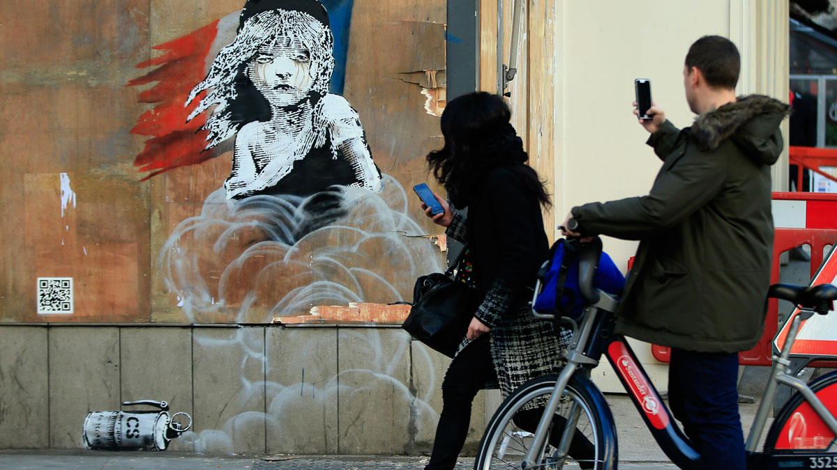 Commuters take photos on their phones of a new artwork by British artist Banksy opposite the French Embassy, in London, Monday, Jan. 25, 2016.