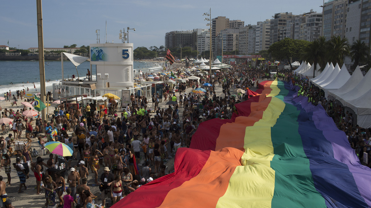 This Dec. 11, 2016, file photo shows people carry a giant gay movement flag during the Gay Pride Parade at Copacabana beach in Rio de Janeiro, Brazil.
