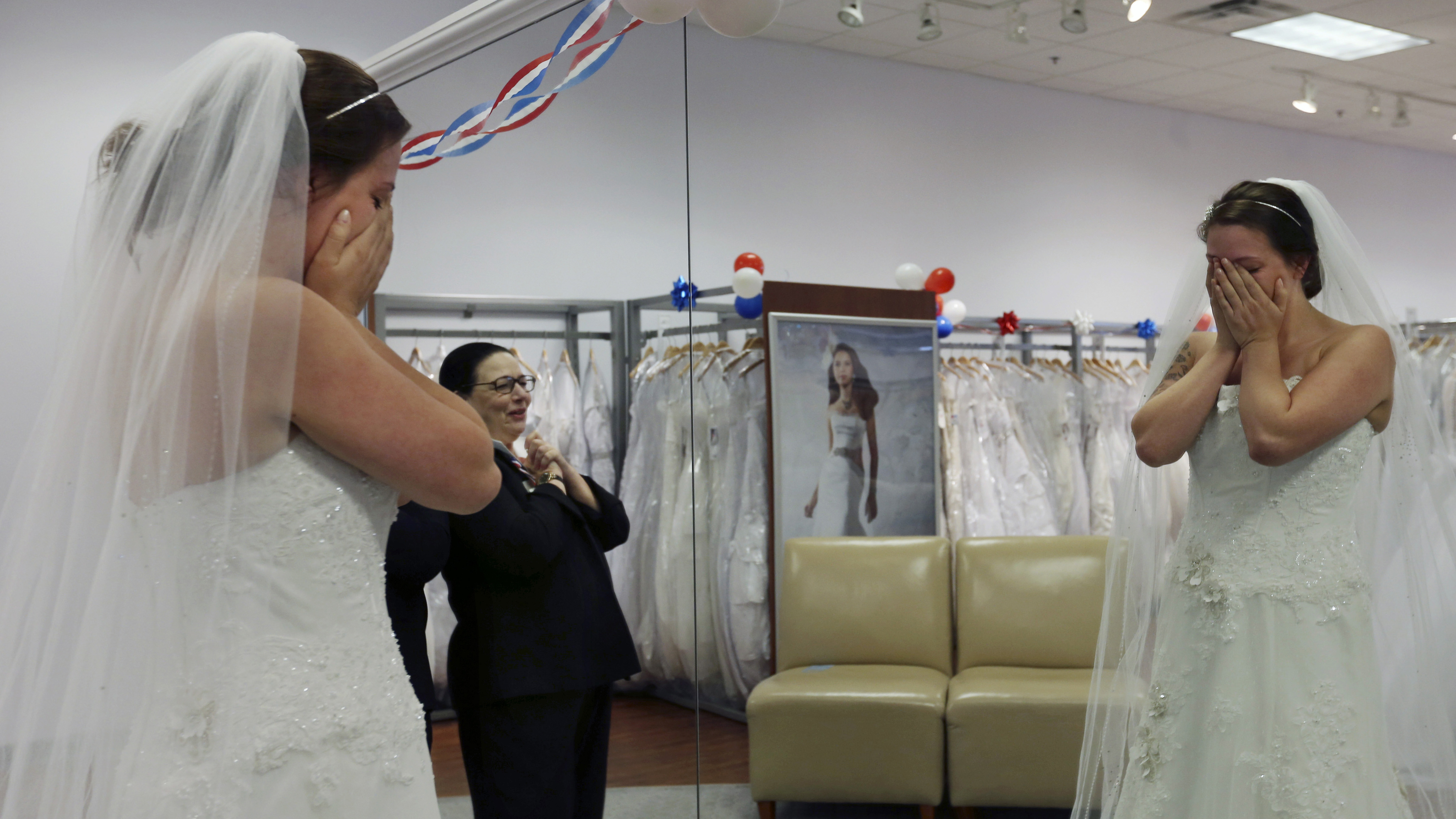Store employee Jo Acchione, left, stands near as former Army National Guard member, Jennifer Dunn, is overcome as she chooses a wedding gown at Alfred Angelo Bridal, Wednesday, Nov. 11, 2015, in Cherry Hill, N.J. The company closed all of its stores on Thursday and filed for Chapter 7 Bankruptcy Friday.