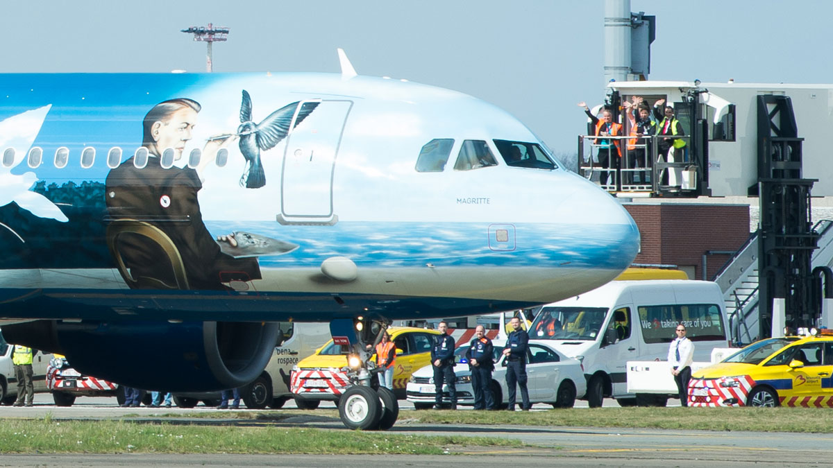Airport workers wave as a Brussels Airlines plane taxis towards the runway at Brussels Airport, in Zaventem, Belgium, Sunday, April 3, 2016. Under extra security, three Brussels Airlines flights, the first for Faro in Portugal, were scheduled to leave Sunday from an airport that is used to handling about 600 flights a day.