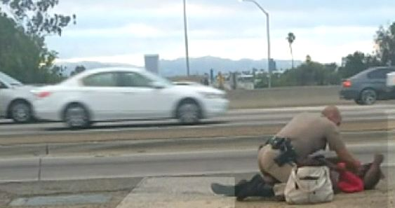 In this still photo of a YouTube video, a CHP officer appears to be hitting a woman in a freeway median.
