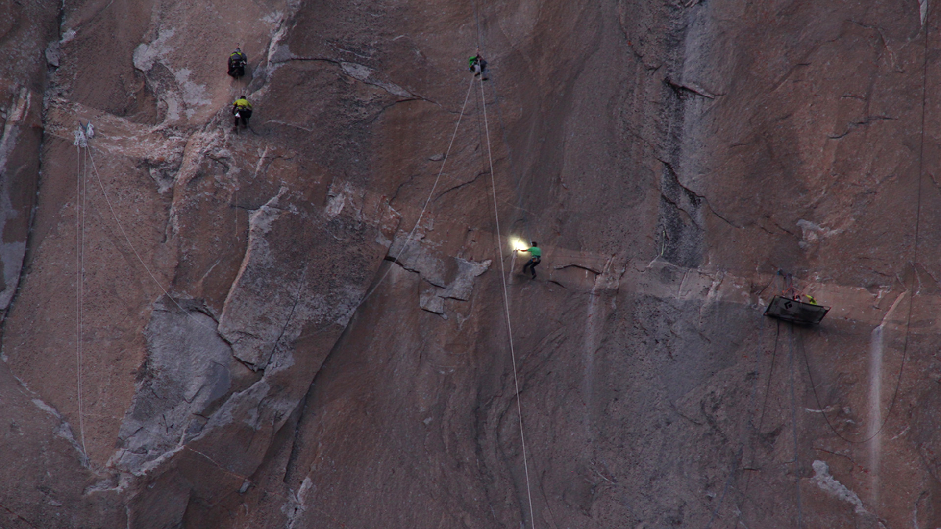 Kevin Jorgeson of Santa Rosa (center, in green) navigating Pitch 15 while Tommy Caldwell (far right, in yellow) of Colorado fixes a running rope around a cleat.  Multiple cameramen hang on ropes taking photos and video. Jan. 7, 2015