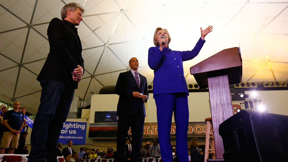 Democratic presidential candidate Hillary Clinton stands on stage with musician Bon Jovi, left, and Sen. Cory Booker, D-N.J., while speaking during a campaign stop at the Newark campus of Rutgers University, on June 1, 2016, in Newark, N.J.