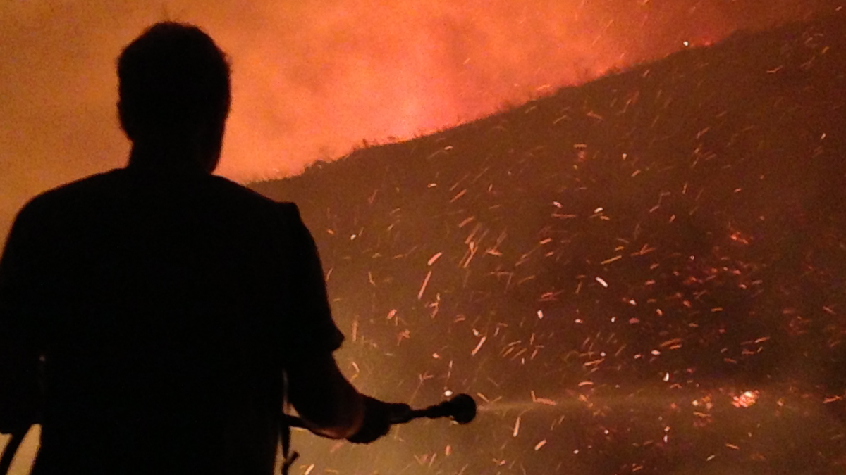 A homeowner hoses down his property while watching flames come close to his home in Coronado Hills.