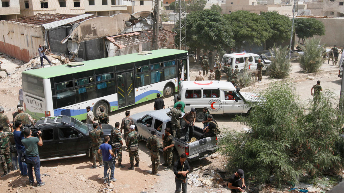 Syrian government buses and a number of the Syrian Arab Red Crescent ambulances at the entrance of Daraya, a suburb of Damascus, Syria on Aug. 26, 2016. The development in the Daraya suburb is part of an agreement struck between the rebels and the government of President Bashar Assad. Rebels in Daraya agreed to evacuate after four years of grueling bombardment and a crippling siege that has left the sprawling suburb southwest of the capital in ruins.