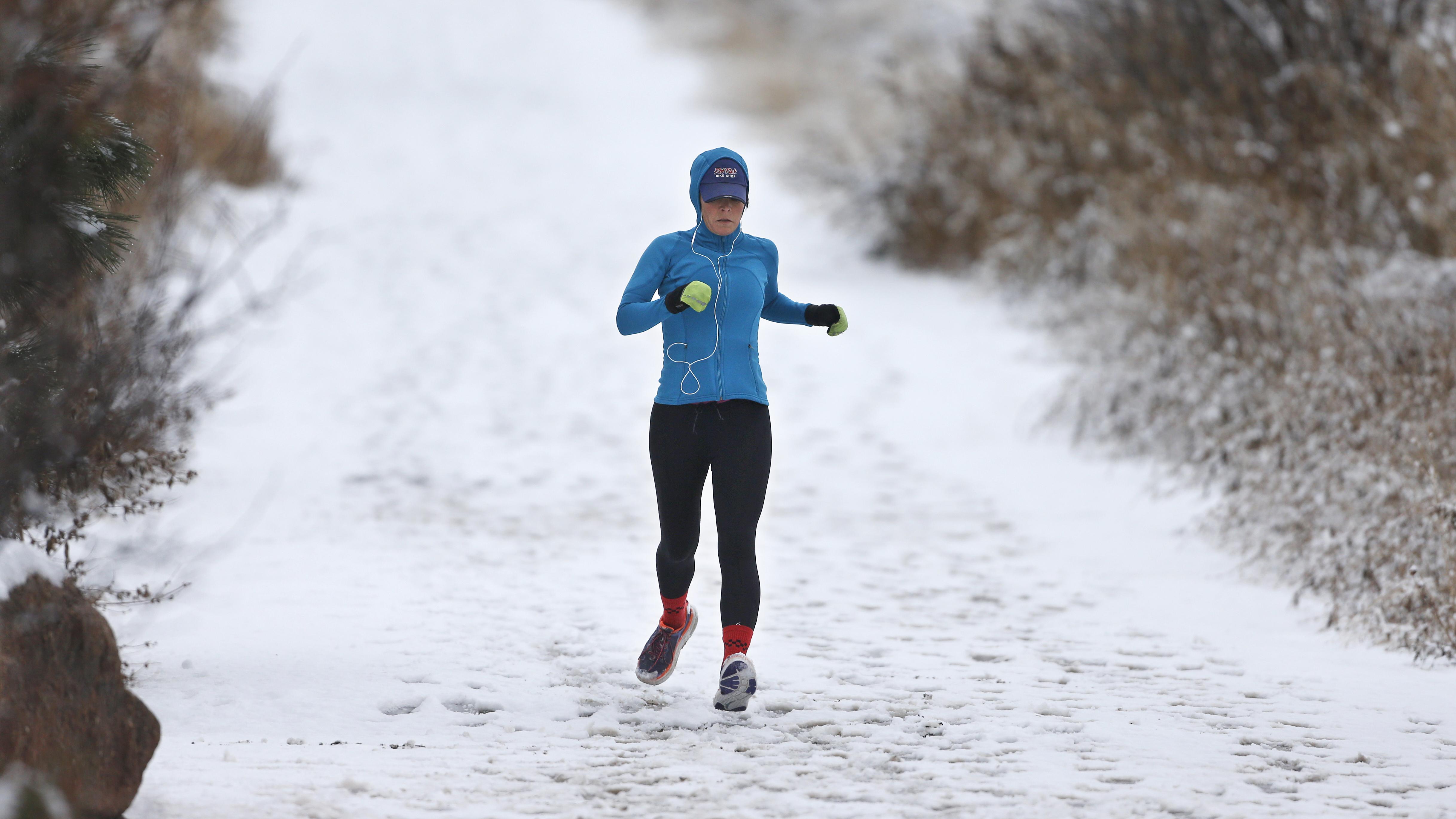 A woman runs in fresh snow at Chautauqua Park, in Boulder, Colo.