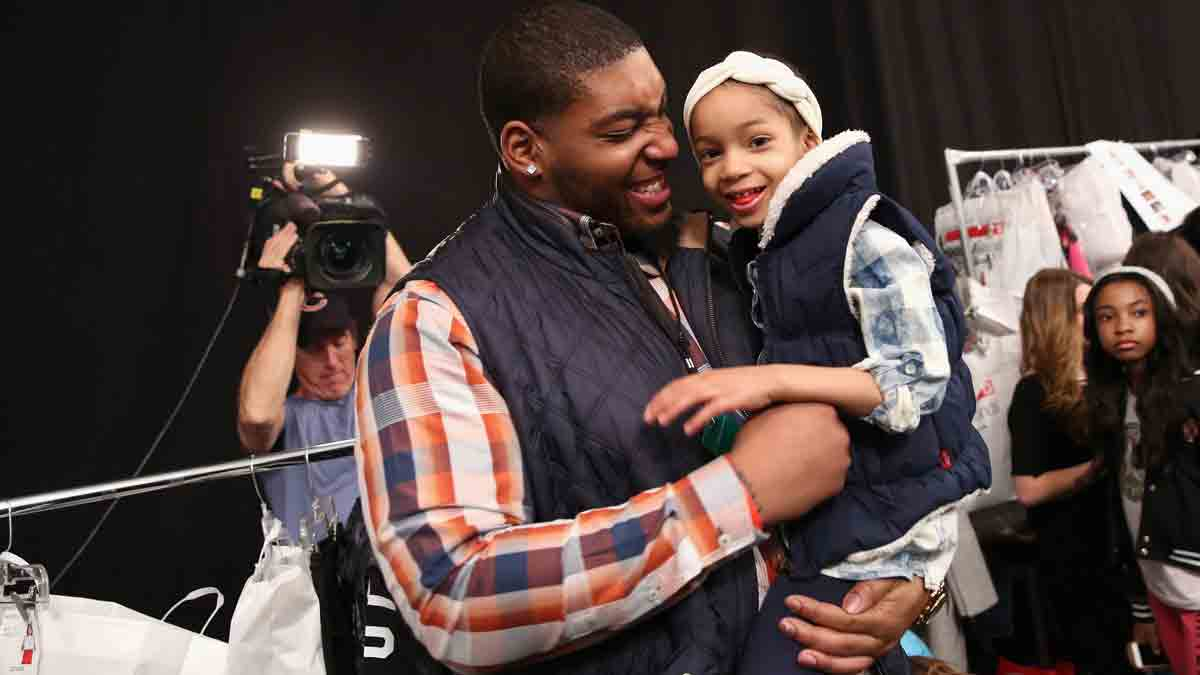 NFL player Devon Still (L) and daughter, prepare backstage at the Nike Levi's Kids fashion show during Mercedes-Benz Fashion Week Fall 2015 at The Salon at Lincoln Center on February 12, 2015 in New York City.