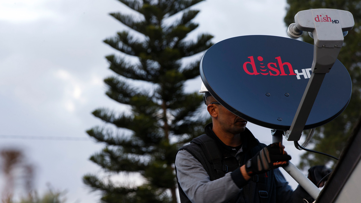 A Dish Network Corp. field service specialist installs a satellite television system at a residence in Downey, California, U.S., on Tuesday, Nov. 3, 2015.