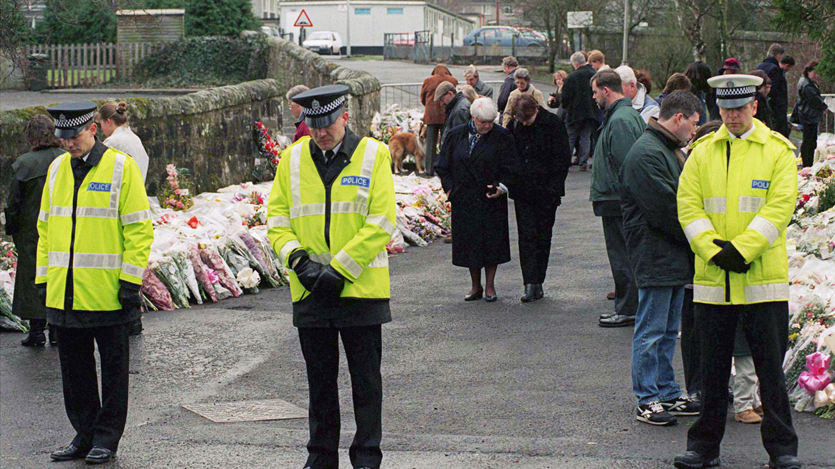 Policemen and members of the community observe a one-minute of silence at Dunblane School in Scotland after a shooting tragedy. Sixteen students and their teacher were shot and killed when a gunman entered the school on March 13, 1996.